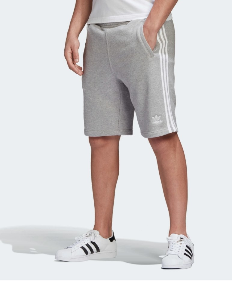 Model wearing gray shorts with white stripes down the side