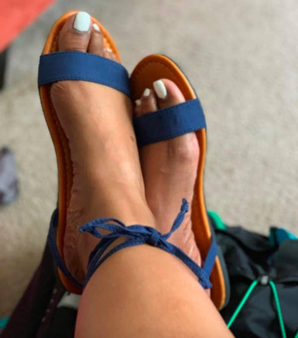 Reviewer wearing the blue strappy sandals