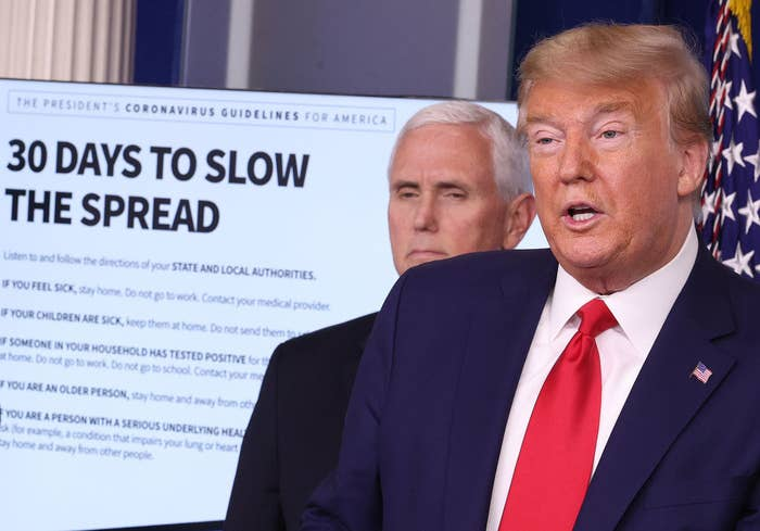 """Donald Trump and Mike Pence standing with a screen behind them with the headline """"33 Days to Slow the Spread"""""""