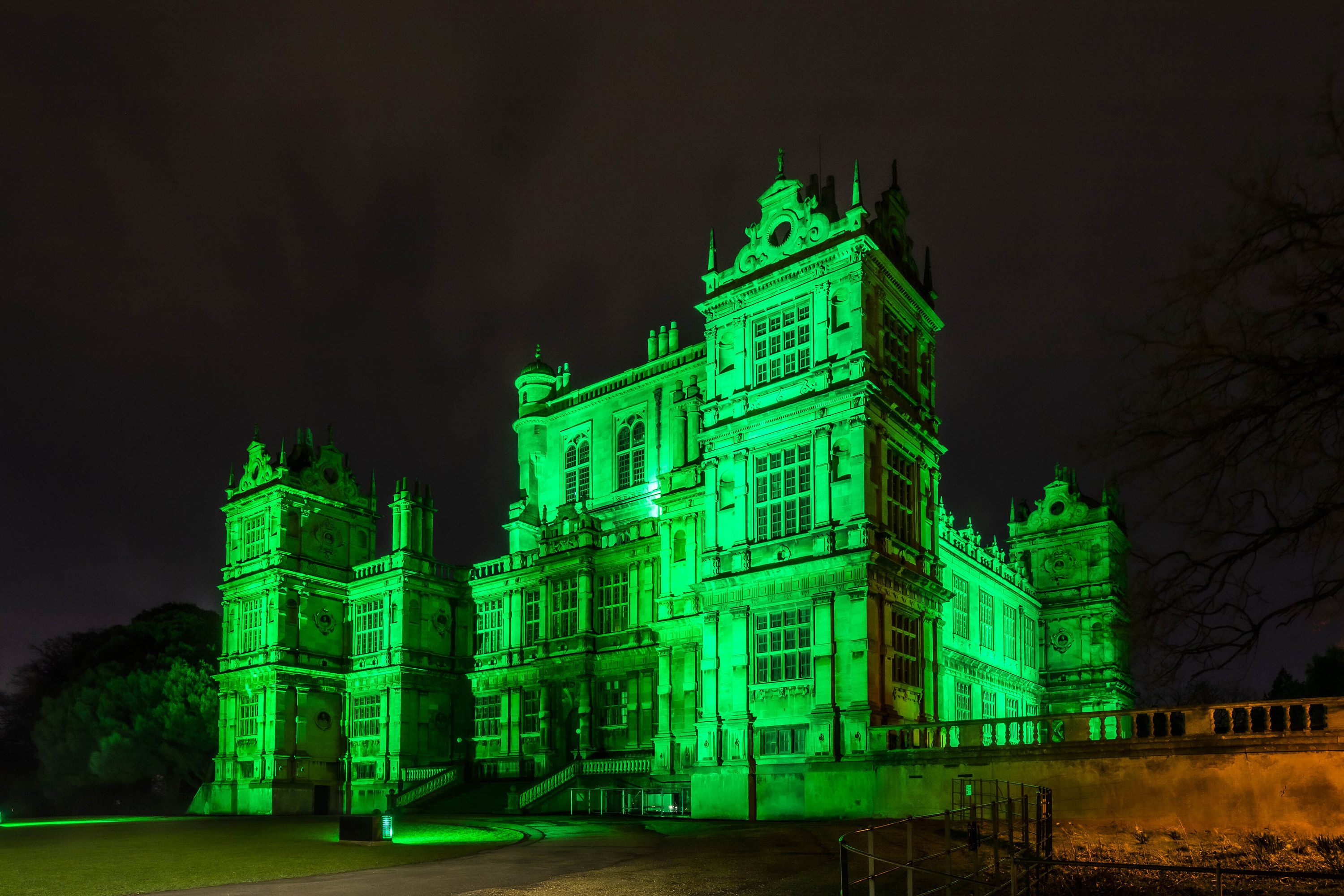 A castle lit up with green lights in honor of St Patricks day