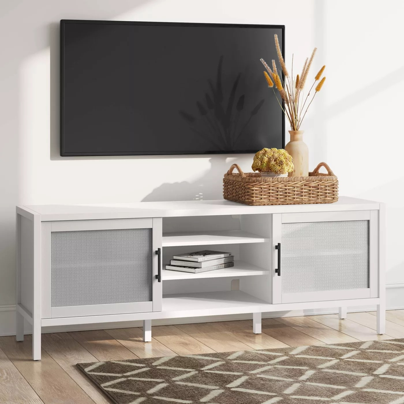 The TV stand with three separate storage compartments placed underneath a mounted TV