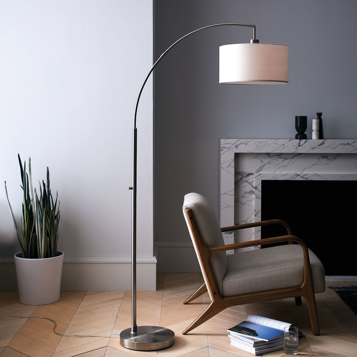 silver arc lamp with an off white lamp shade next to a grey armchair