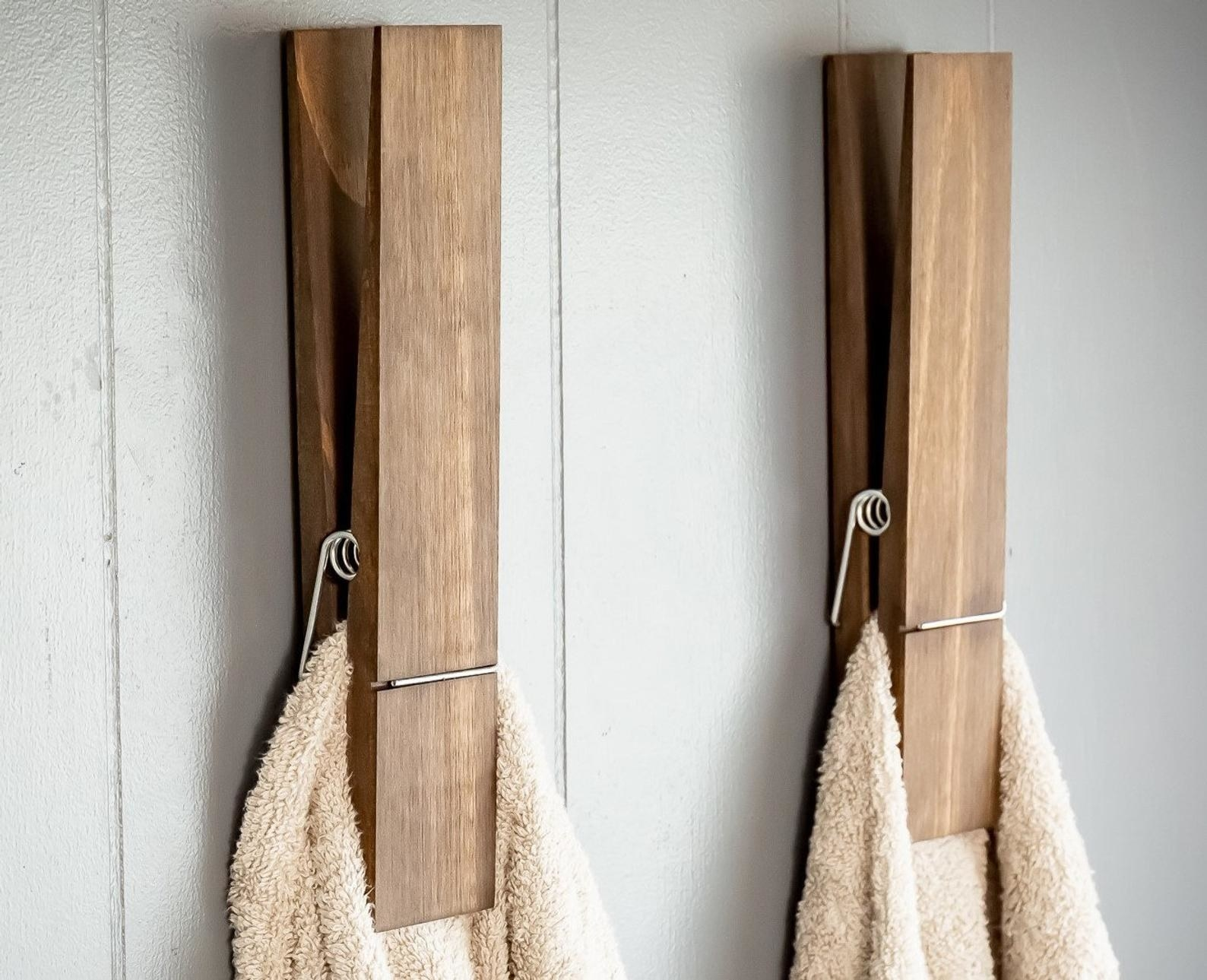 two jumbo clothespin towel holders mounted to a wall, each holding a beige towel