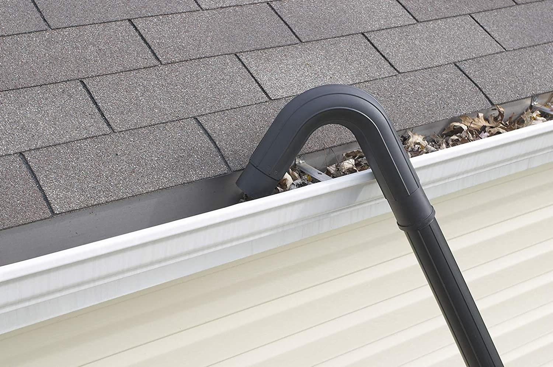 The curved hose sucking up debris inside a gutter