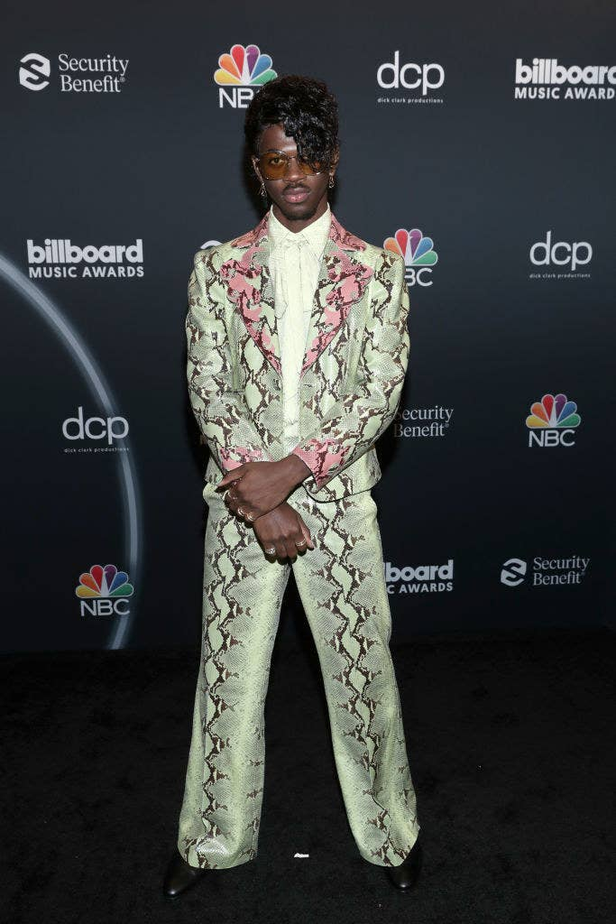 Lil Nas posing on a red carpet in a snakeskin inspired suit, sunglasses, and rocking bangs