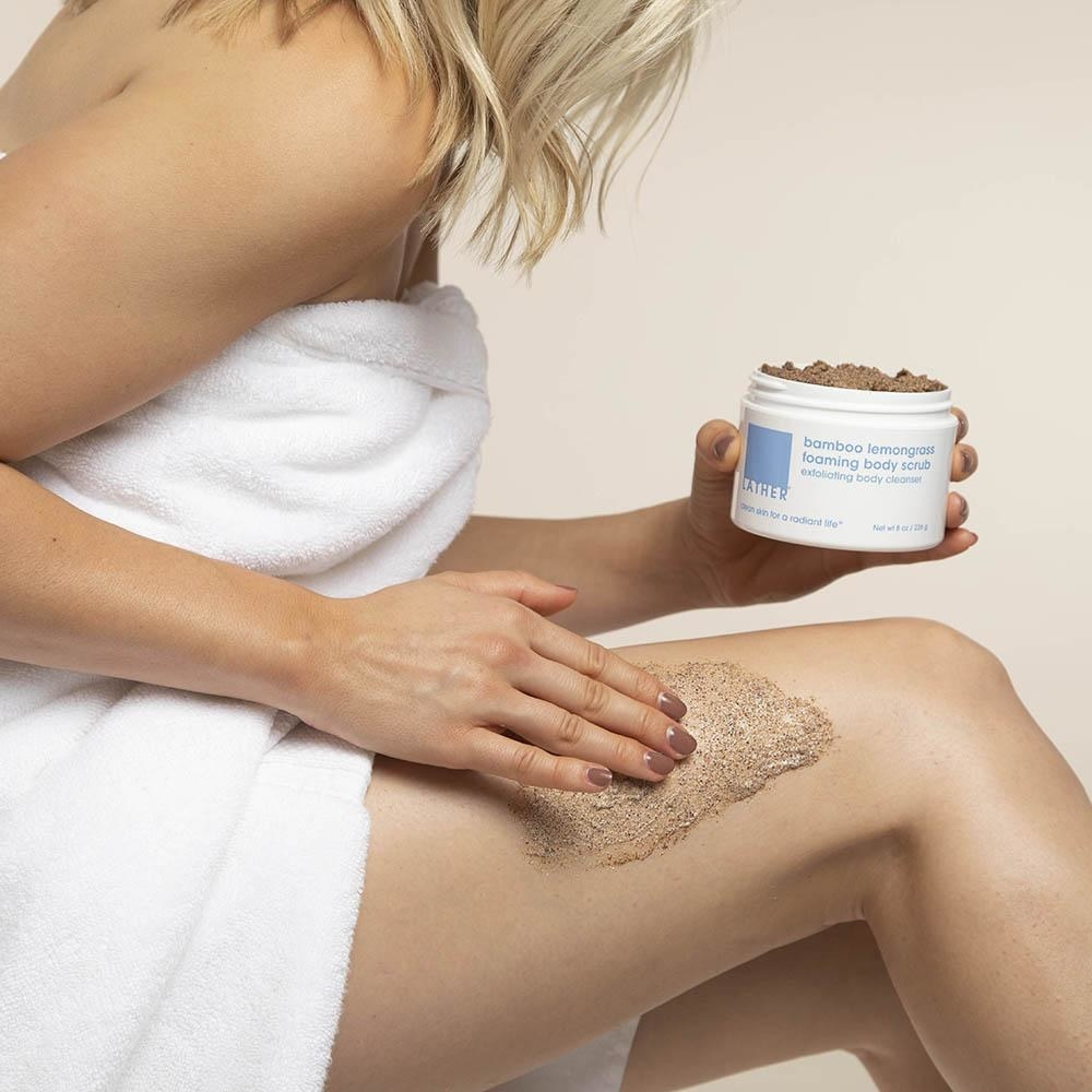 model rubs the body scrub on their legs
