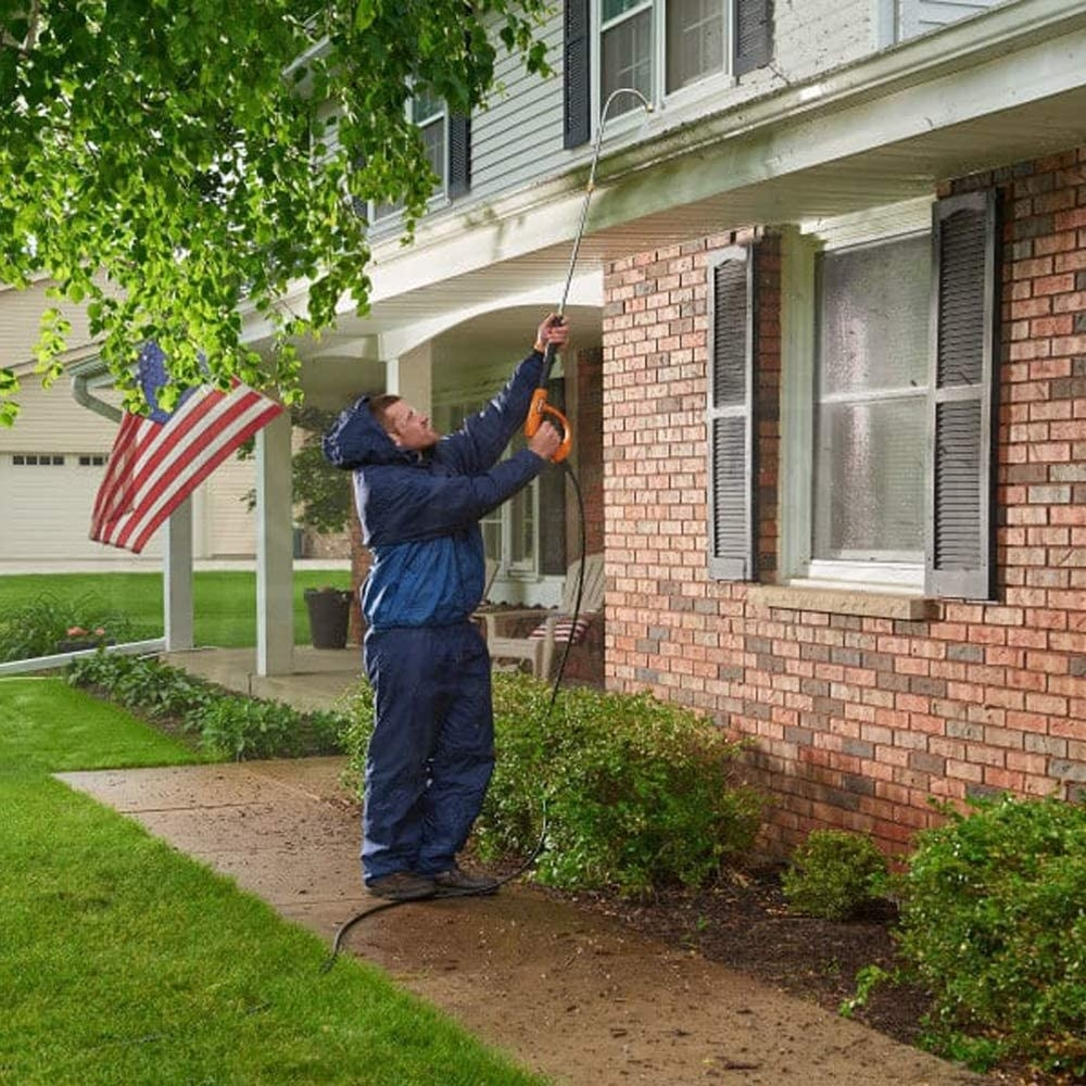 Person standing on the ground cleaning their gutters using the curved tube attached to a pressure washer to clean gutters