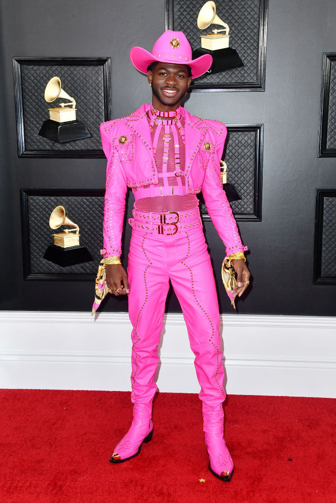 Lil Nas rocking a hot pink suit with cropped jacket, cowboy boots, harness, and hat as well as silk scarves around his wrists