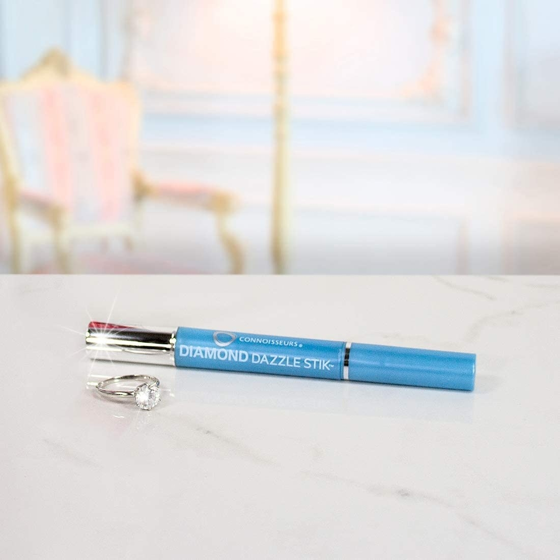 the diamond cleaning pen on a table next to a ring