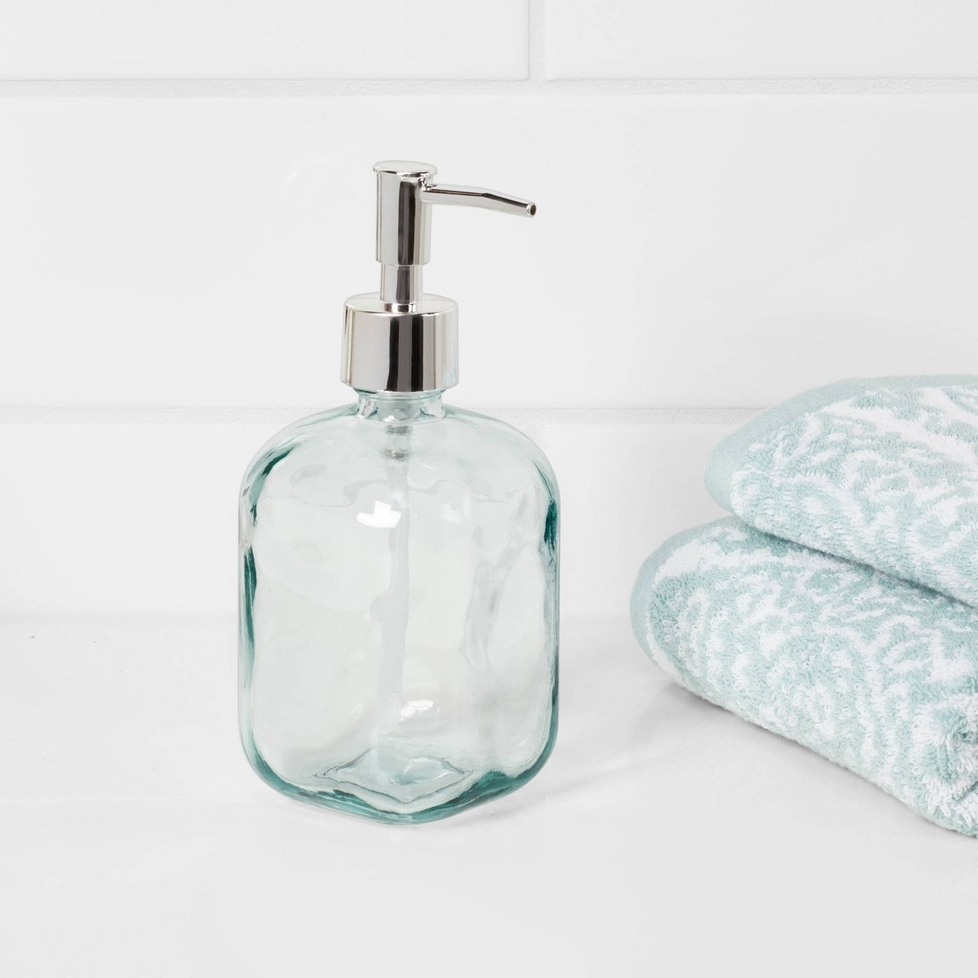 clear rounded rectangular glass soap dispenser with silver pump