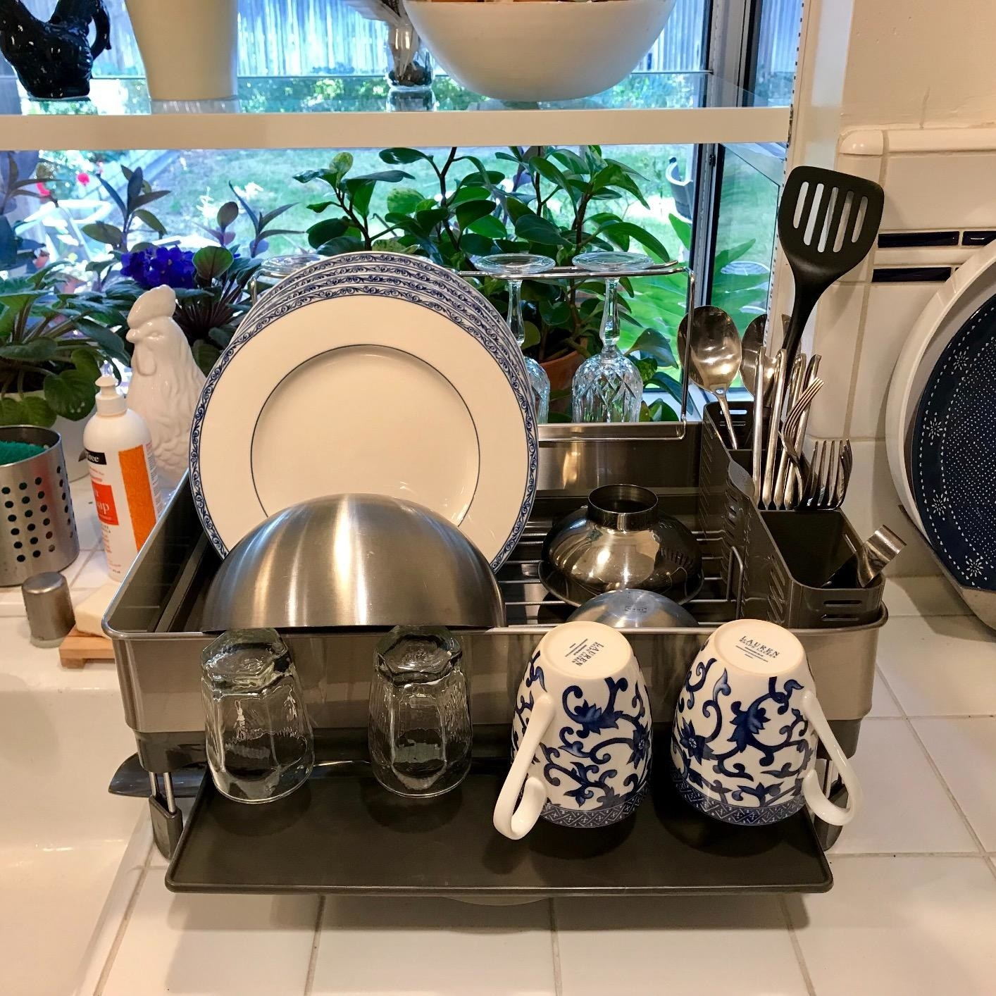 The dish rack, which has dedicated areas to dry dishes, silverware, cups and wine glasses
