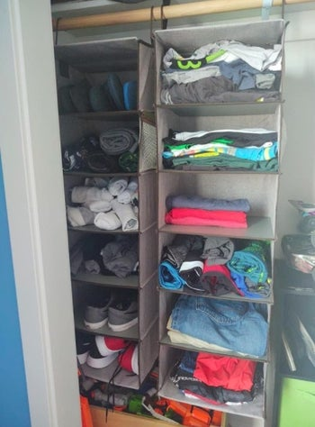 two hanging closet organizers with various clothes in them