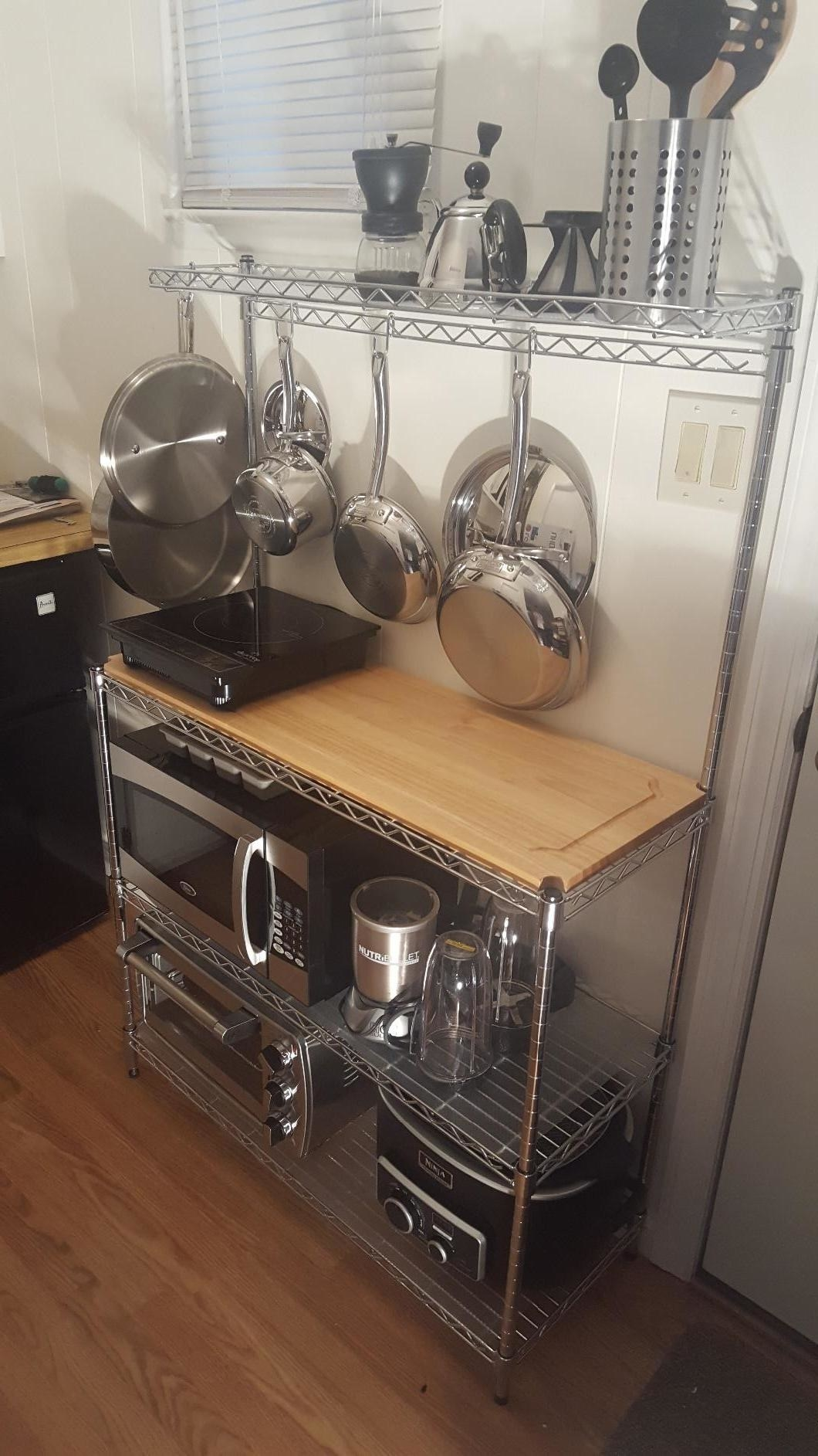 The baker's rack with a microwave, convection oven, and multiple frying pans stored on it