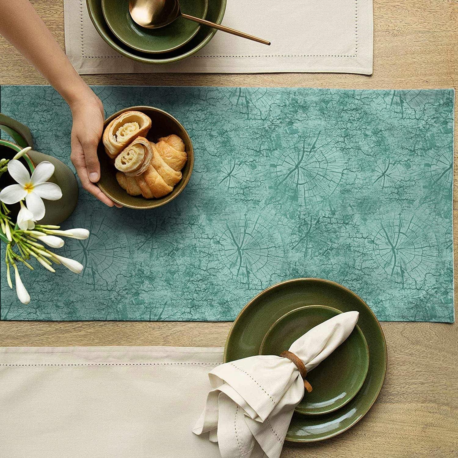 Green plates, napkins, a bowl of croissants, and a plant kept on the table runner.
