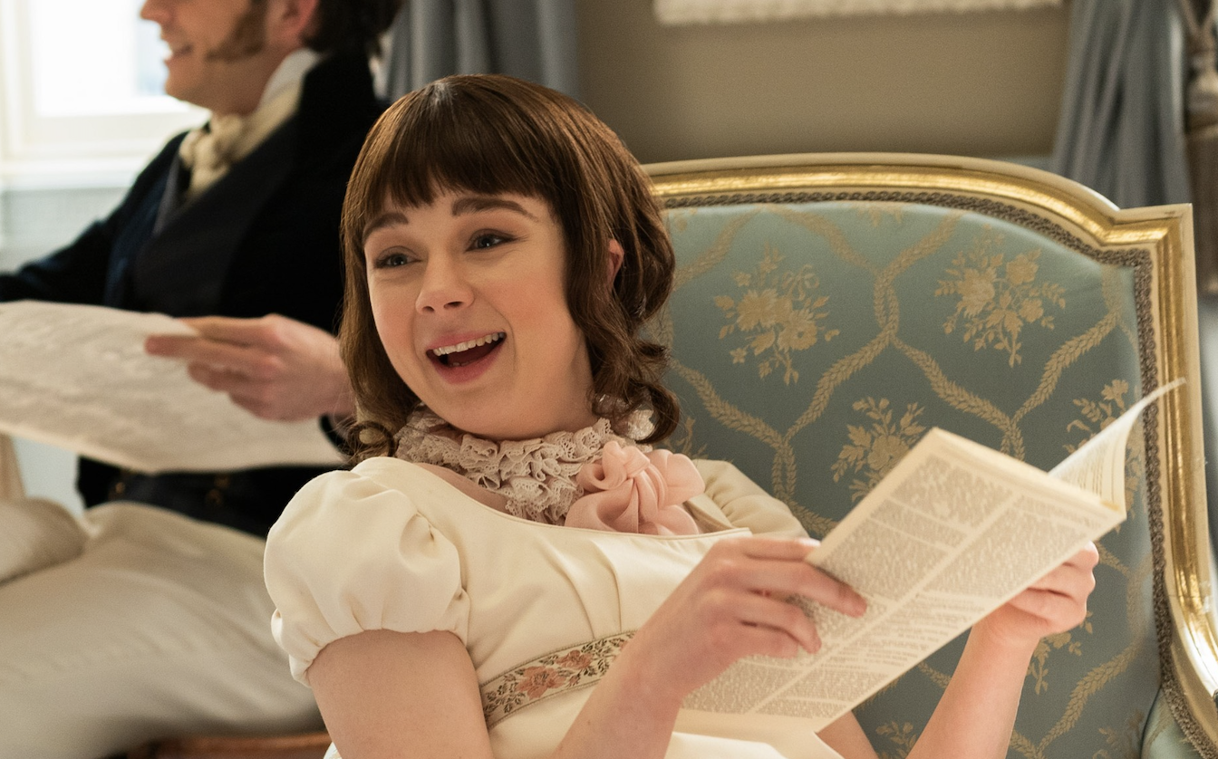Eloise smiling and holding the gossip column in her hands