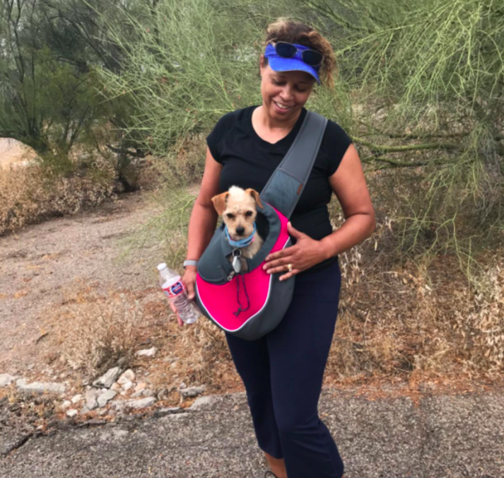 Reviewer walking with small dog in the sling pouch