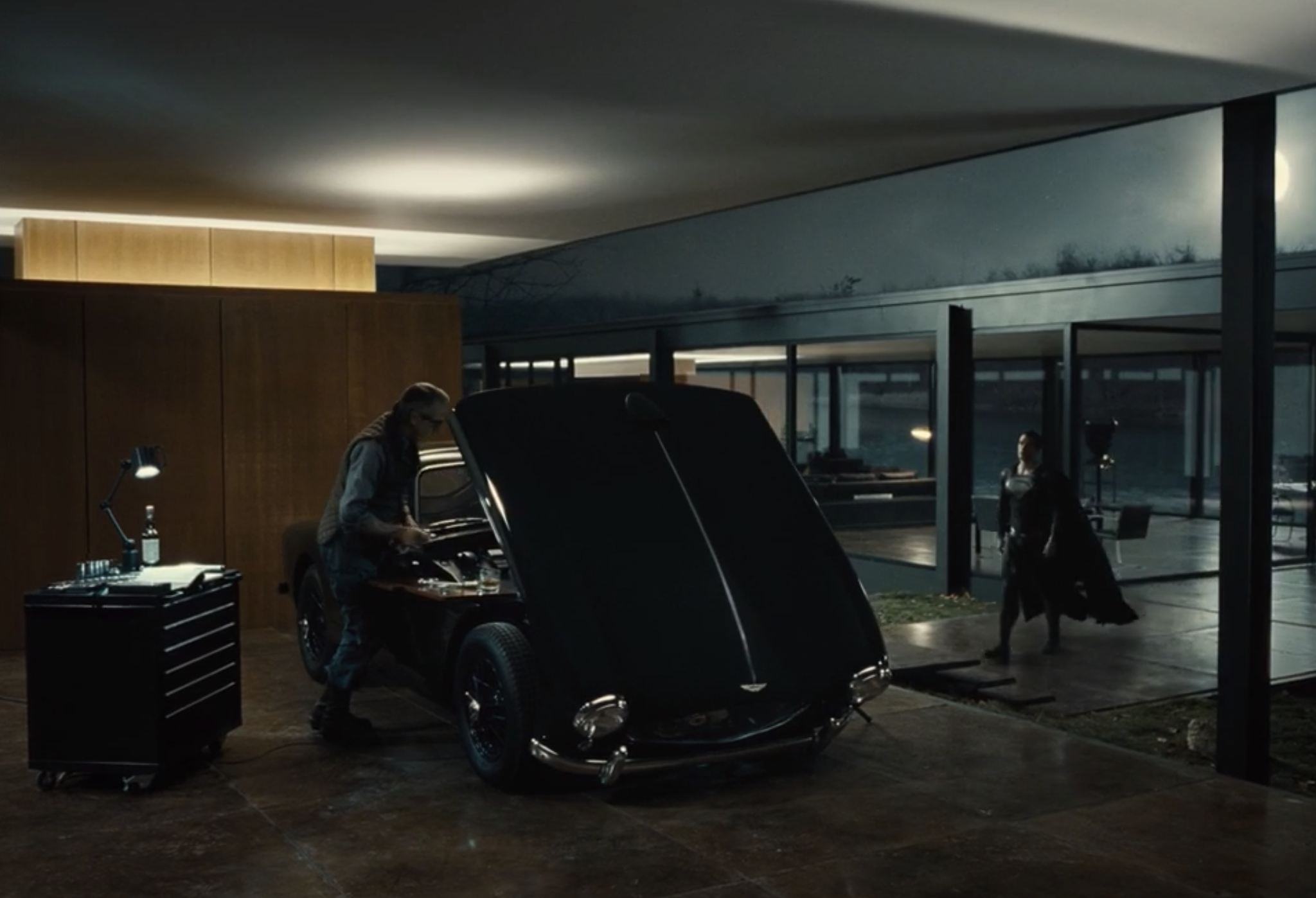 Alfred working on a car as Superman walks up
