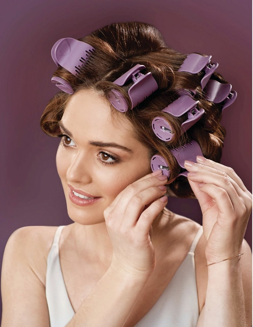 A woman with heated rollers in her head
