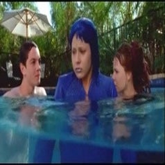 Cybergirl in a pool in her full blue outfit with two people. She looks very uncomfortable