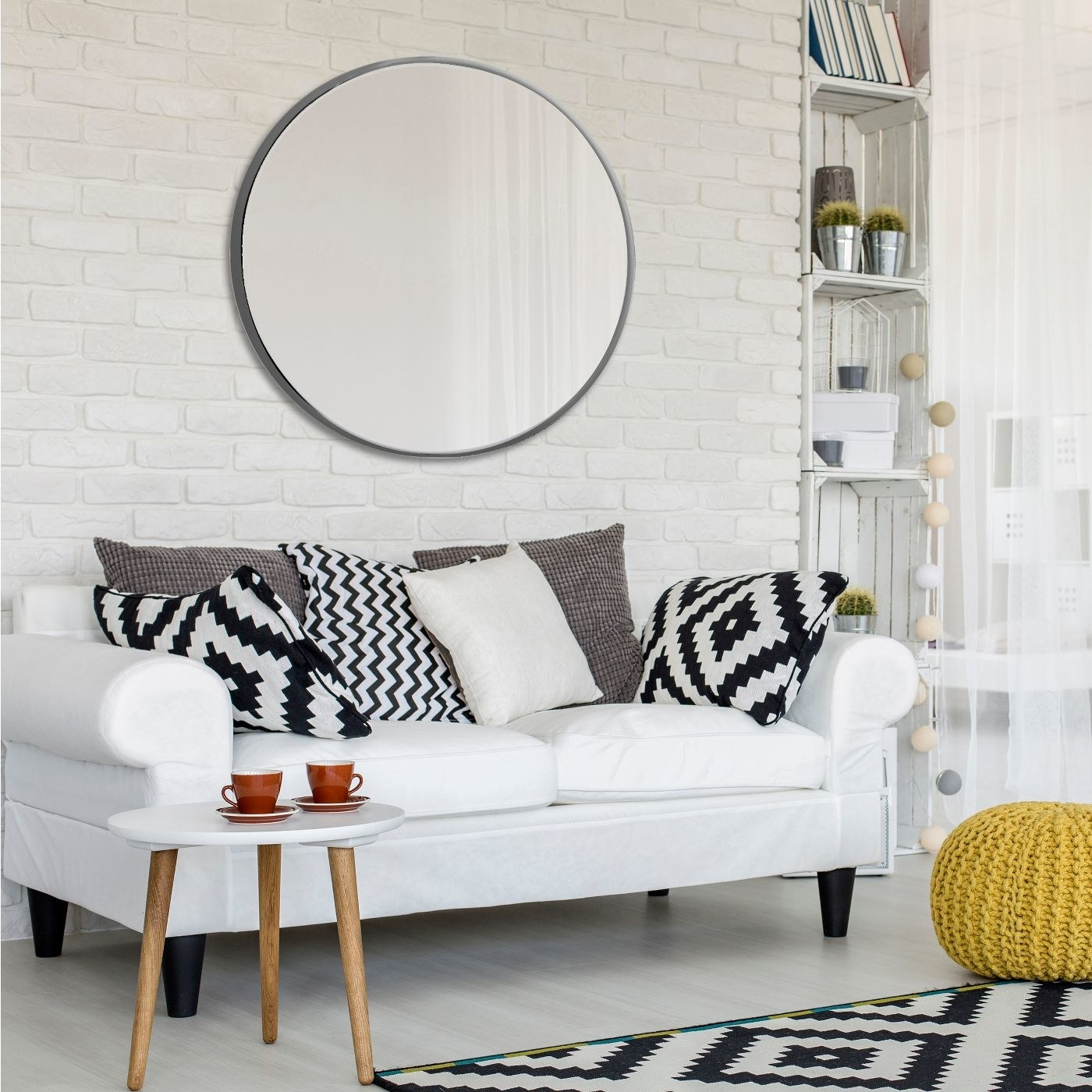 round wall mirror with silver frame hung above white sofa with throw pillows