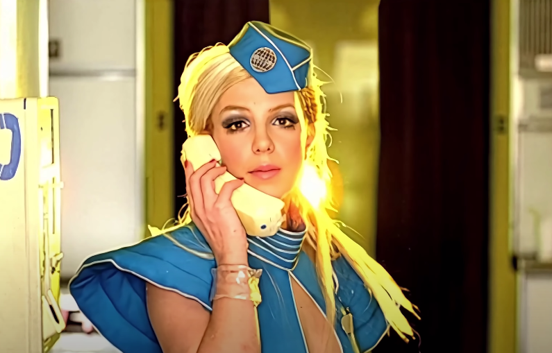 Screenshot of Britney as a stewardess with a phone in her hand in the Toxic video