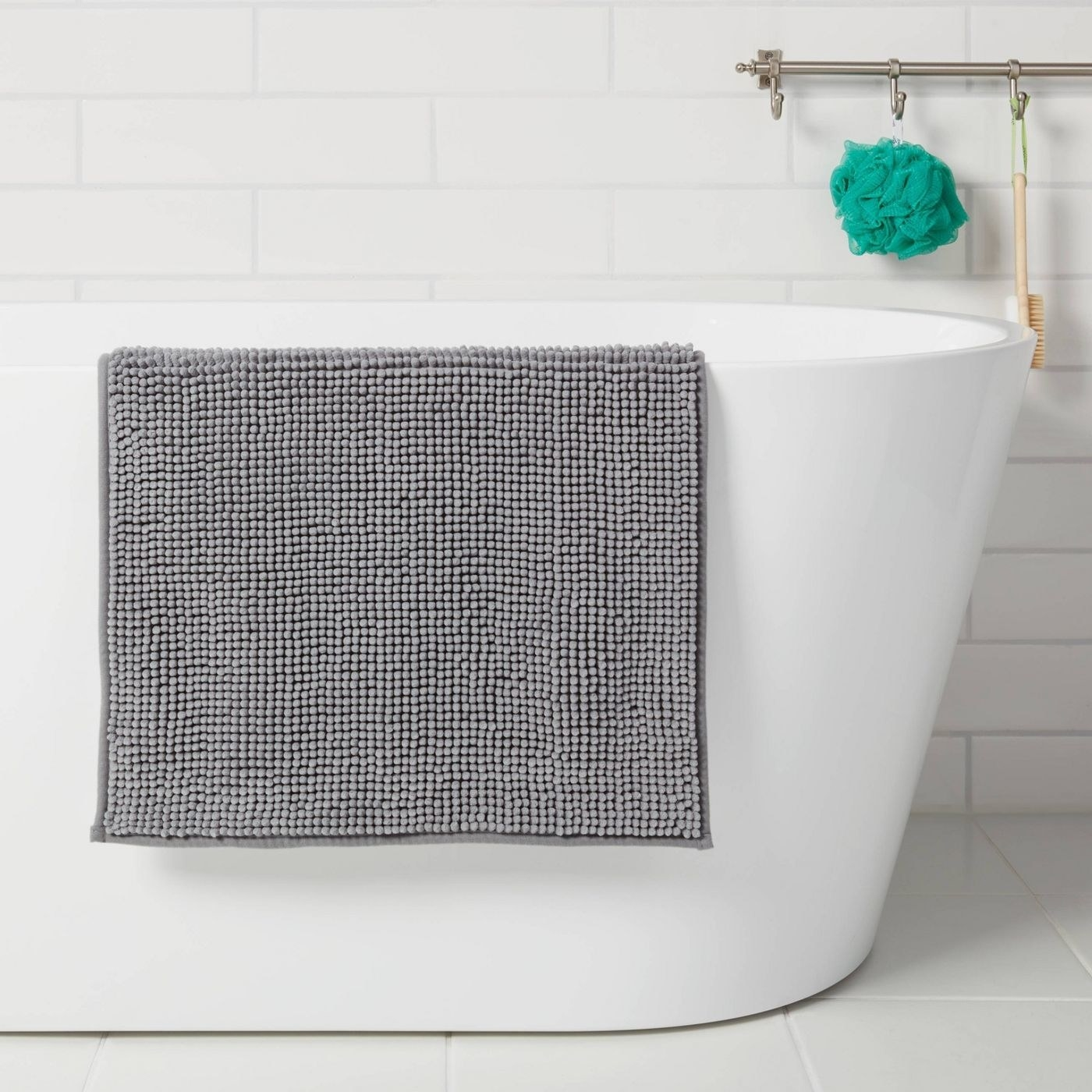 grey bath mat draped over the side of a white bath tub