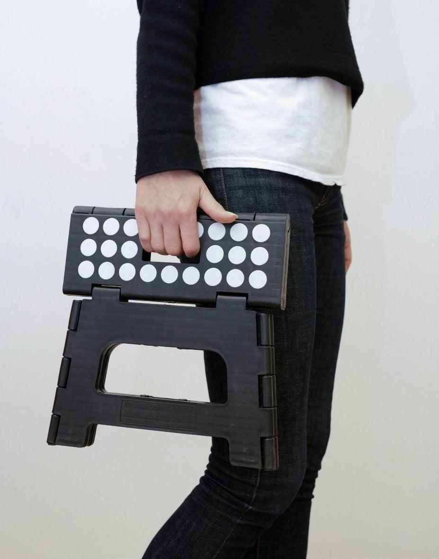 model holding black and white foldable step stool
