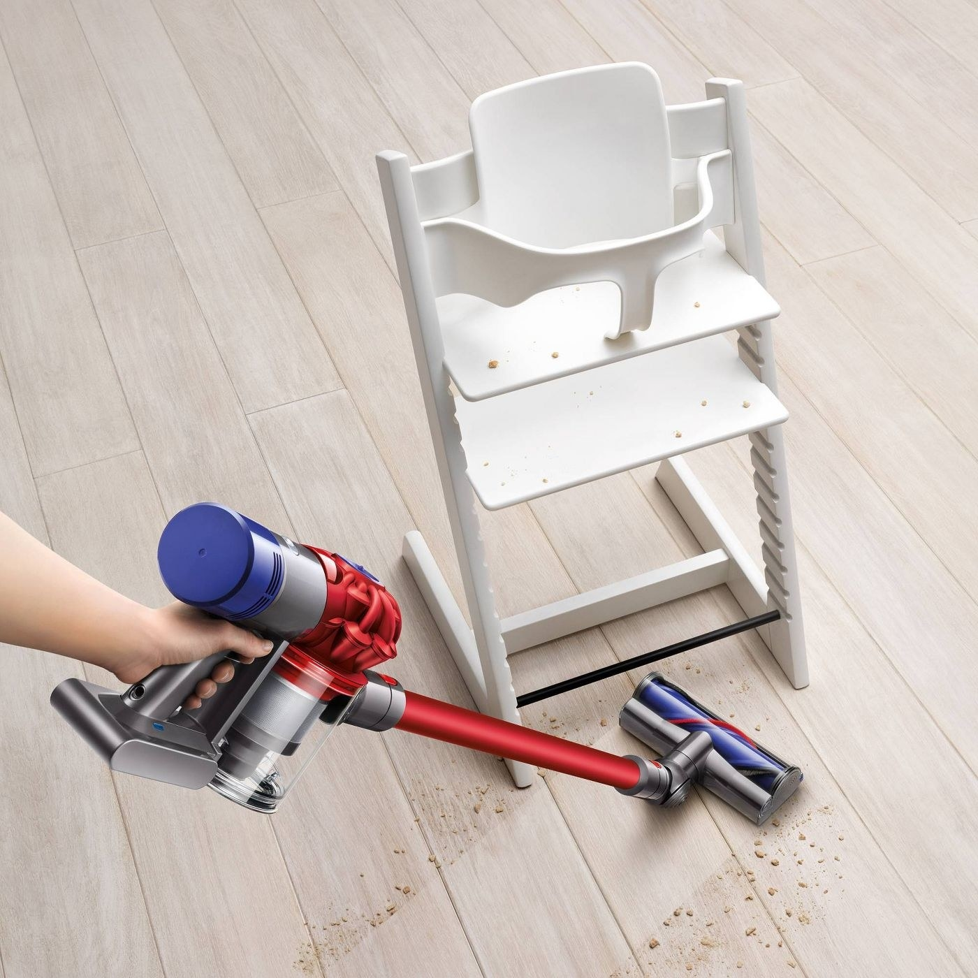 purple and red cordless Dyson stick vacuum cleaning a hardwood floor