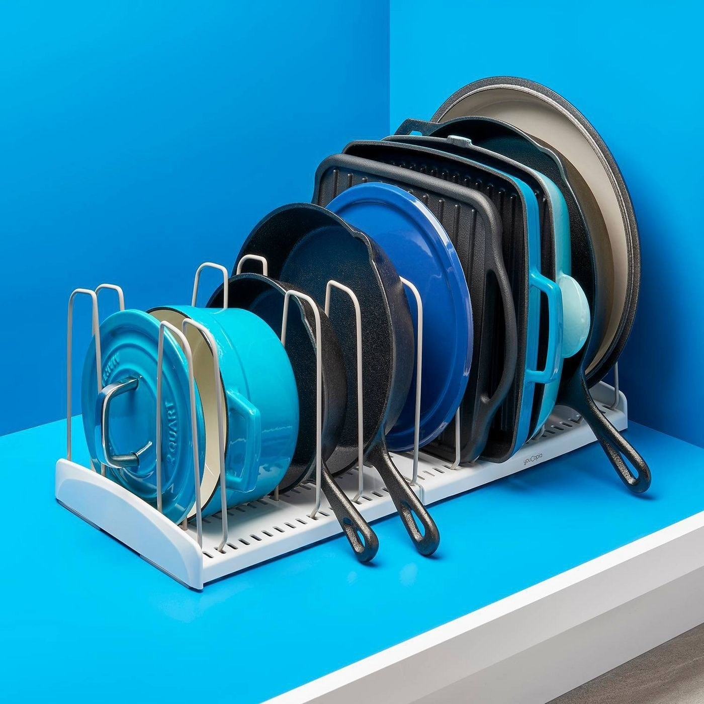 expandable cookware rack filled with various cookware and bakeware lying sideways