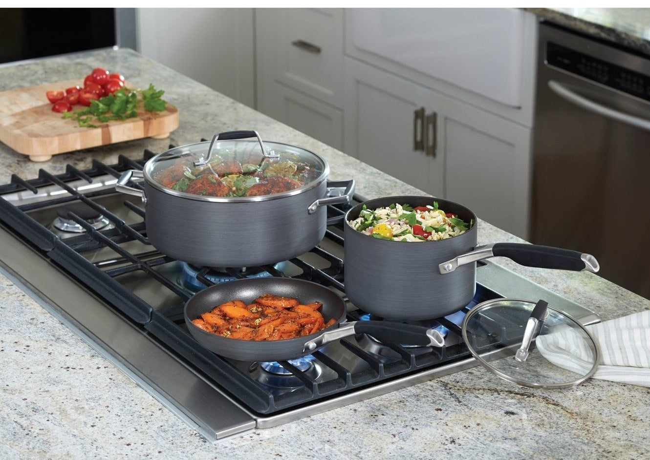 a pan over with cover, sauce pan, and fry pan cooking on a stove