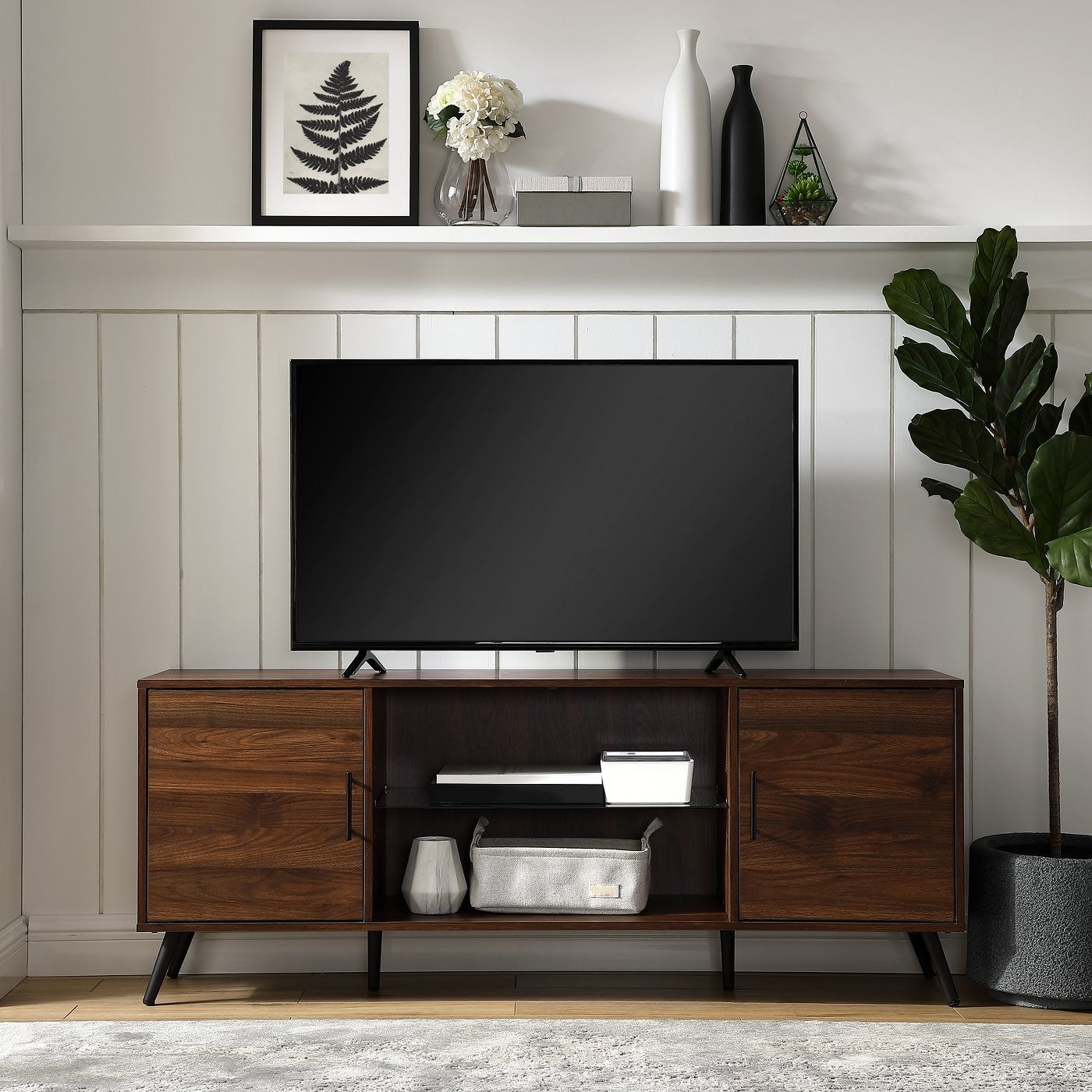 walnut colored media console with two size cabinets and shelves in the middle, with a TV on top