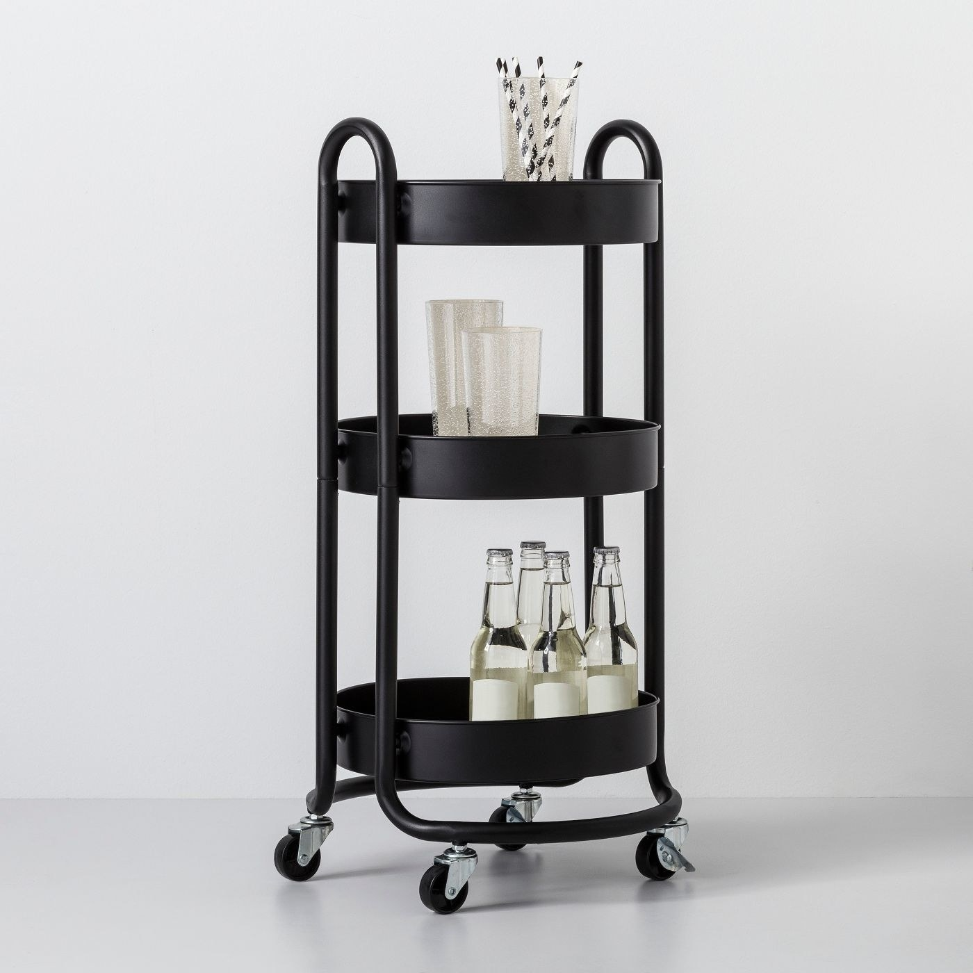 black round metal utility cart with wheels, with bottles and cups on the shelves