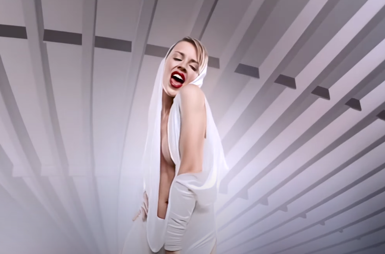 Screenshot of Kylie from the music video with her in a white jumpsuit.