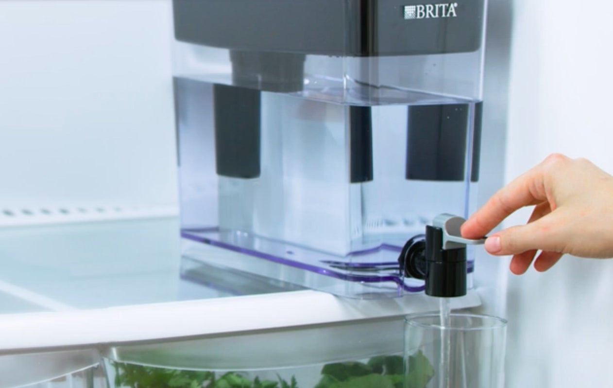 A person dispensing water out of the brita jug and into a glass