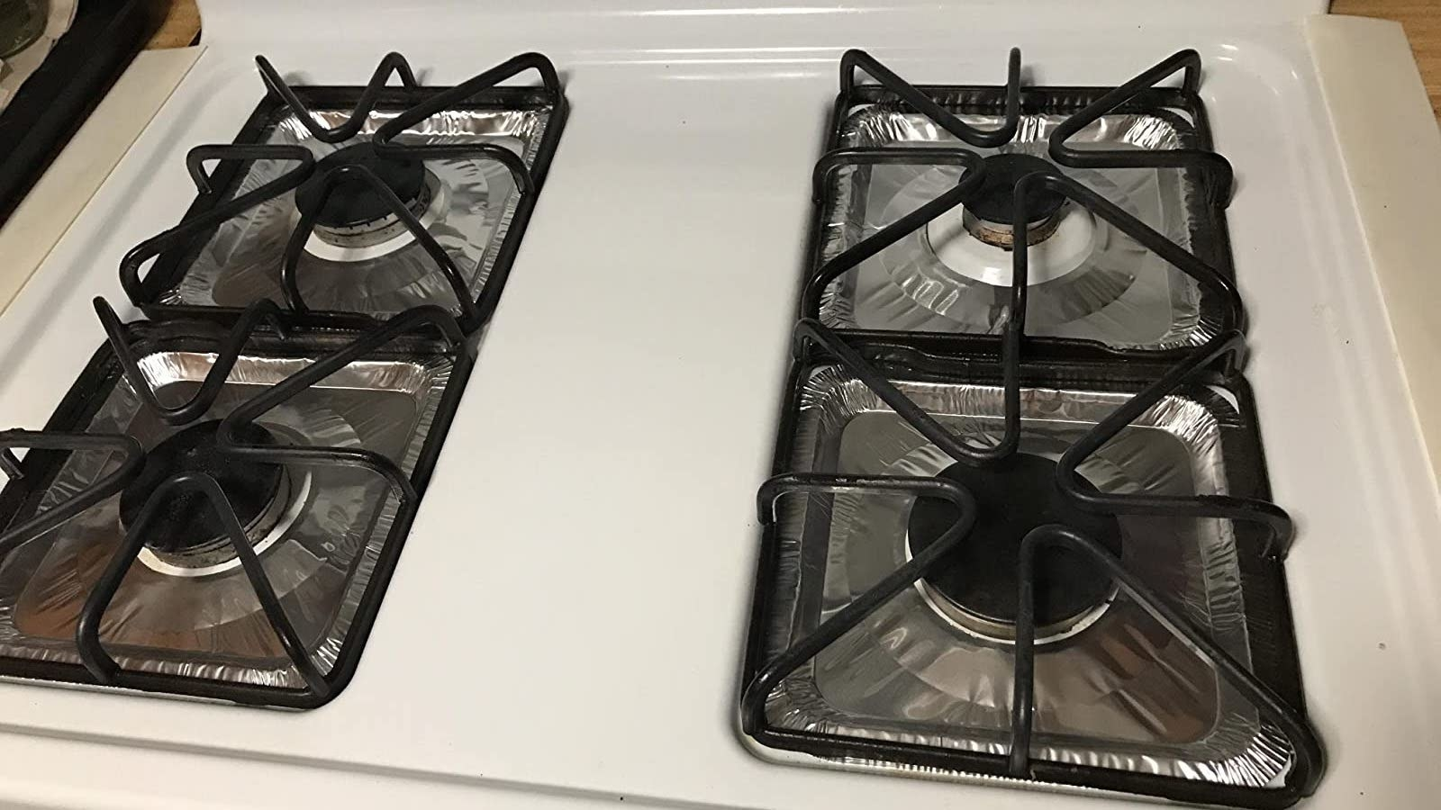 Reviewer photo of foil liners placed on gas stove range