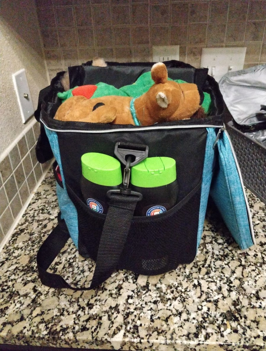 The zip top travel bag full of toys and grooming products in various pockets
