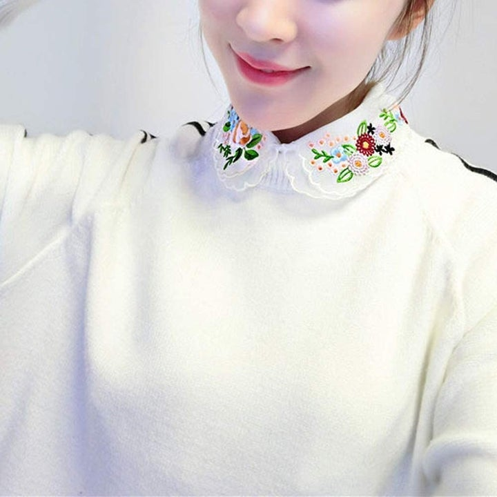 A model wearing the embroidered dicky under a sweater
