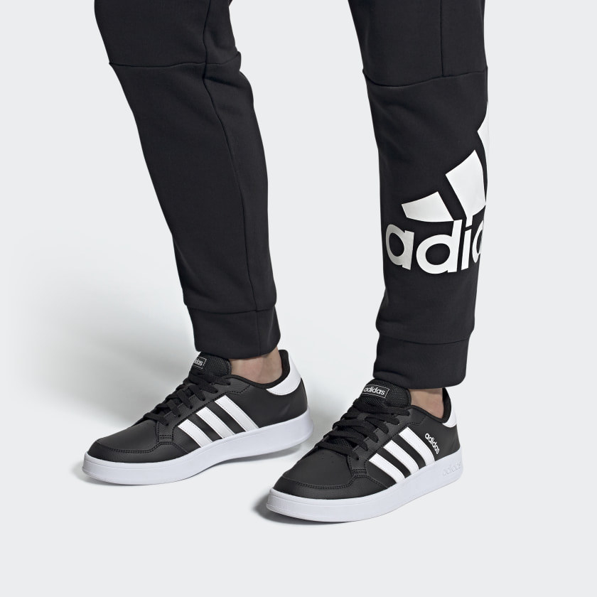 a model wearing matching adidas sneakers and sweatpants