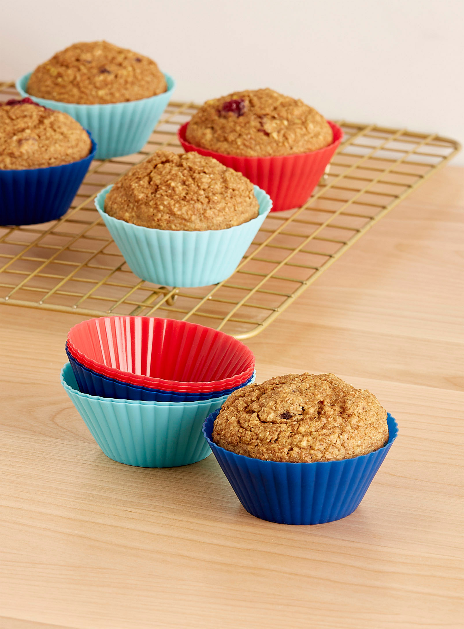 A set of silicone muffin moulds on a cooling rack