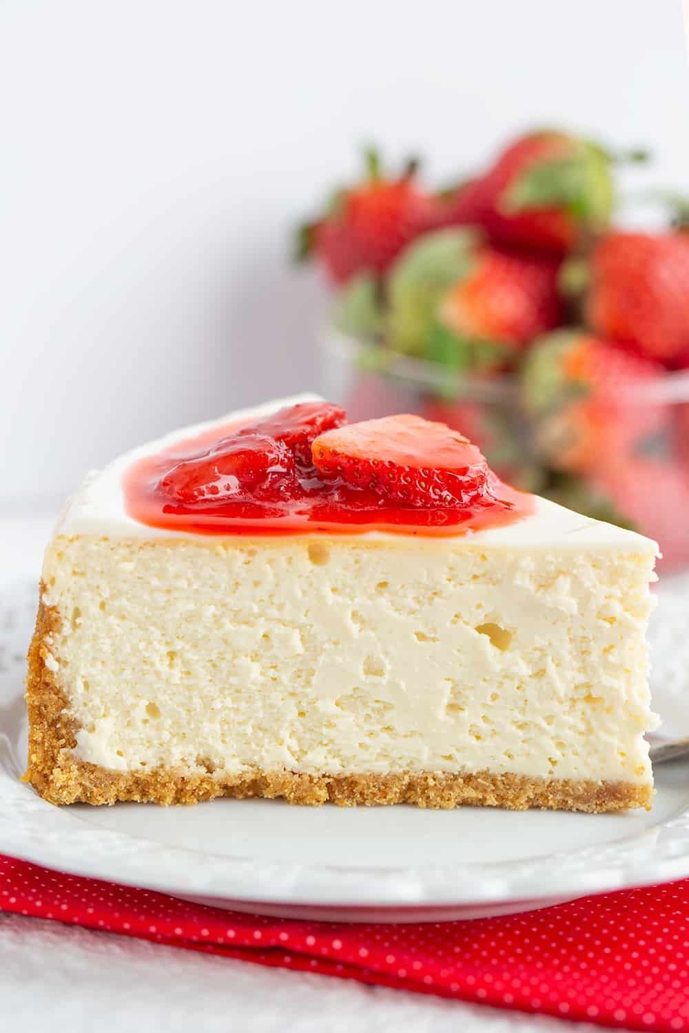 A thick slice of cheesecake with strawberry topping.