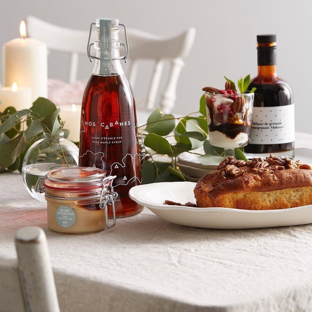 A glass bottle of maple syrup on a table with a small loaf of bread