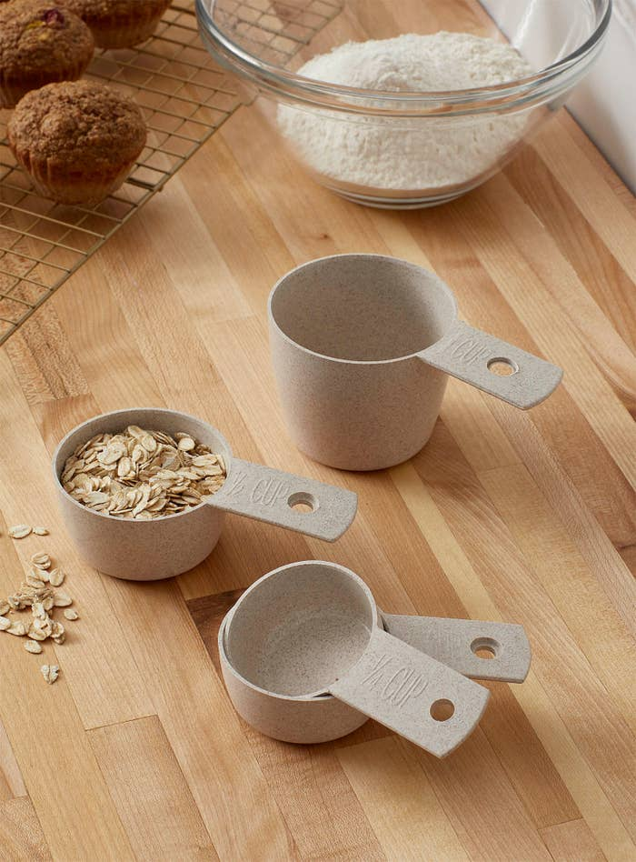 A set of four compostable measuring cups on a cutting boards