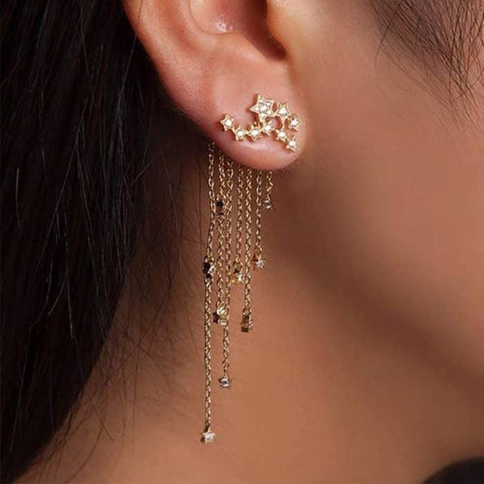 A model wearing the tassel earrings in gold