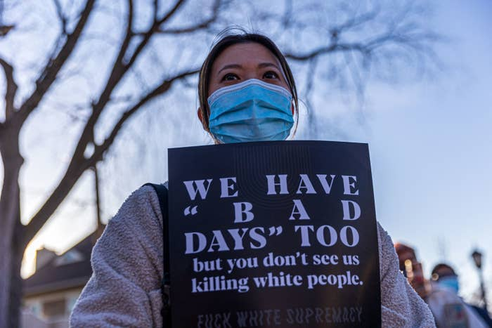 """An Asian American woman stands in a medical mask at a protest with a sign that says, """"We have 'bad days' too but you don't see us killing white people. Fuck white supremacy."""""""