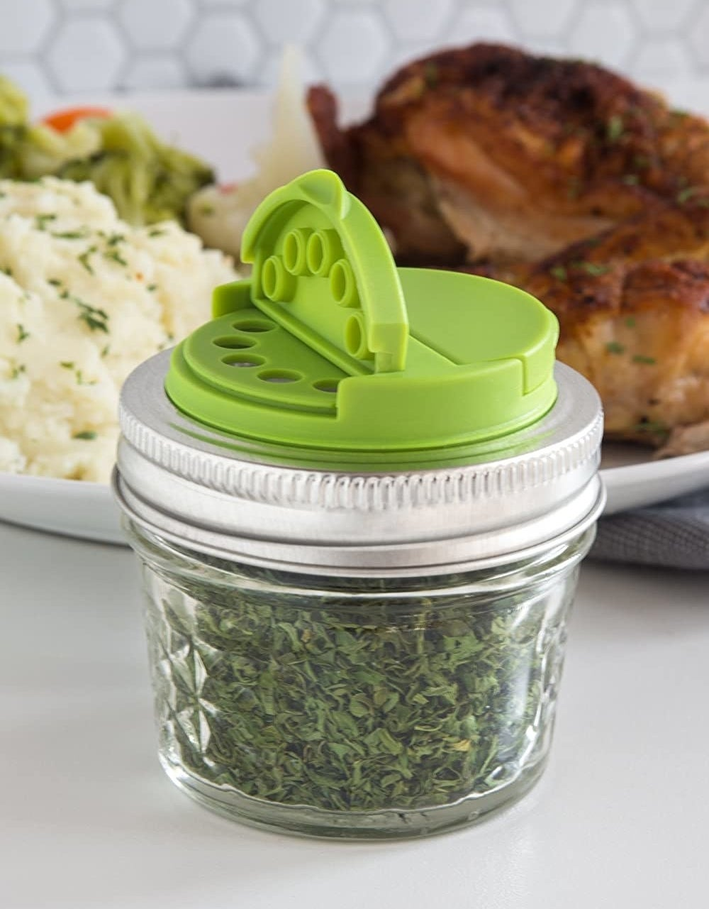 A small spice lid on top of a tiny Mason jar filled with herbs