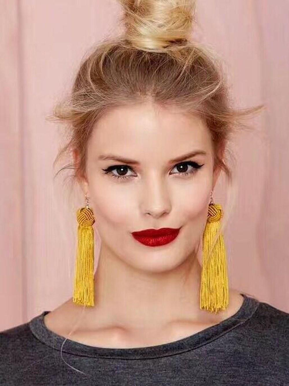 A model wearing the earrings in yellow