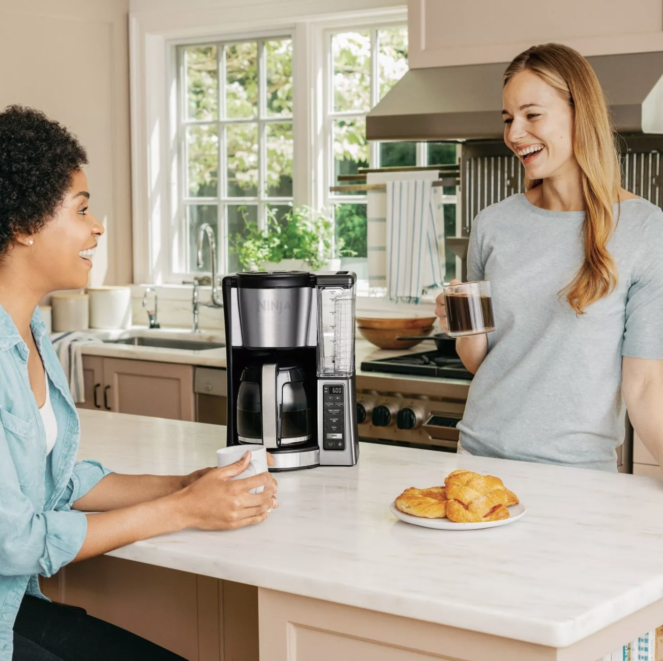 Two people drinking coffee next to the coffee maker