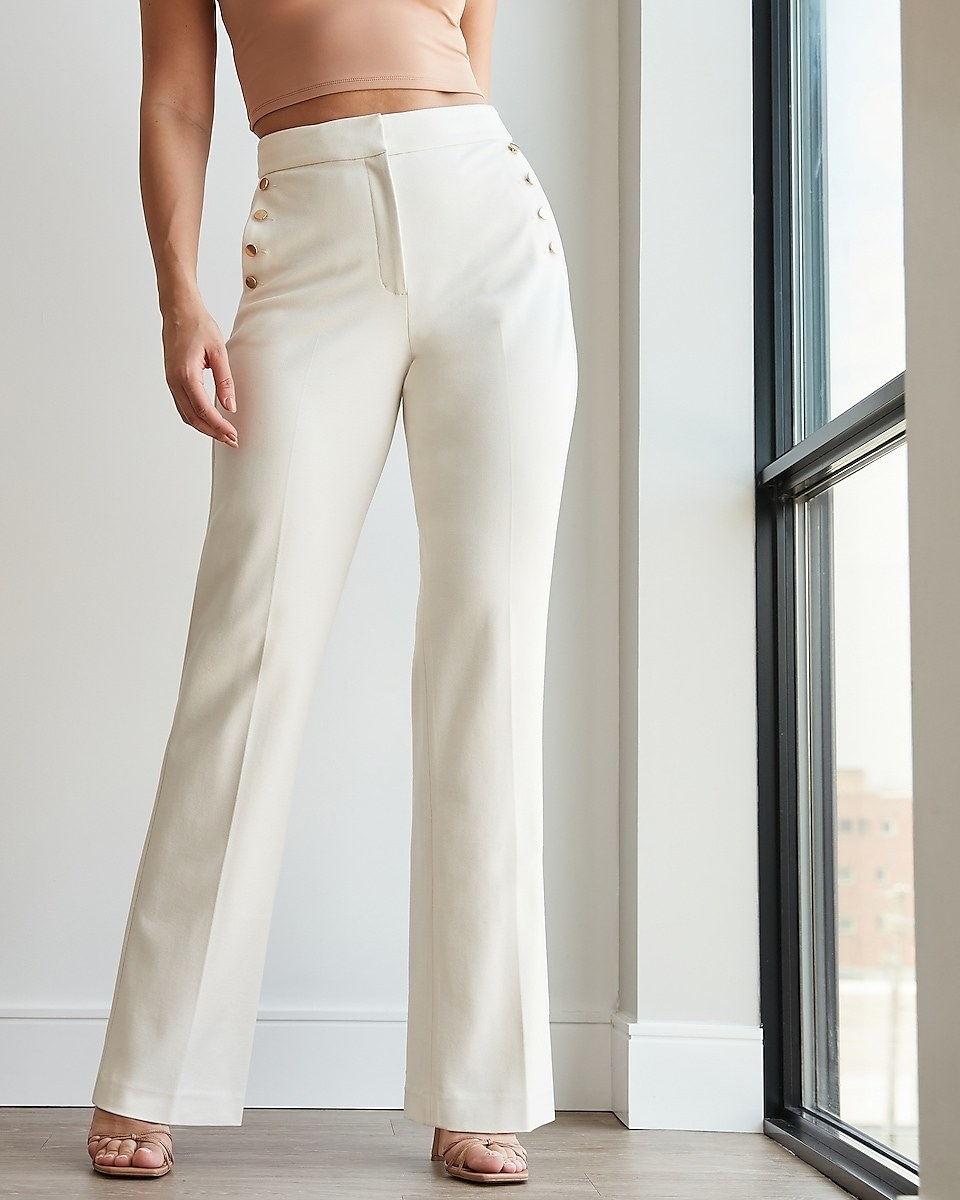 model wearing the white pants with gold button detailing