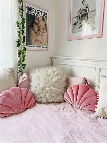 a reviewer's bed with two pink shell pillows