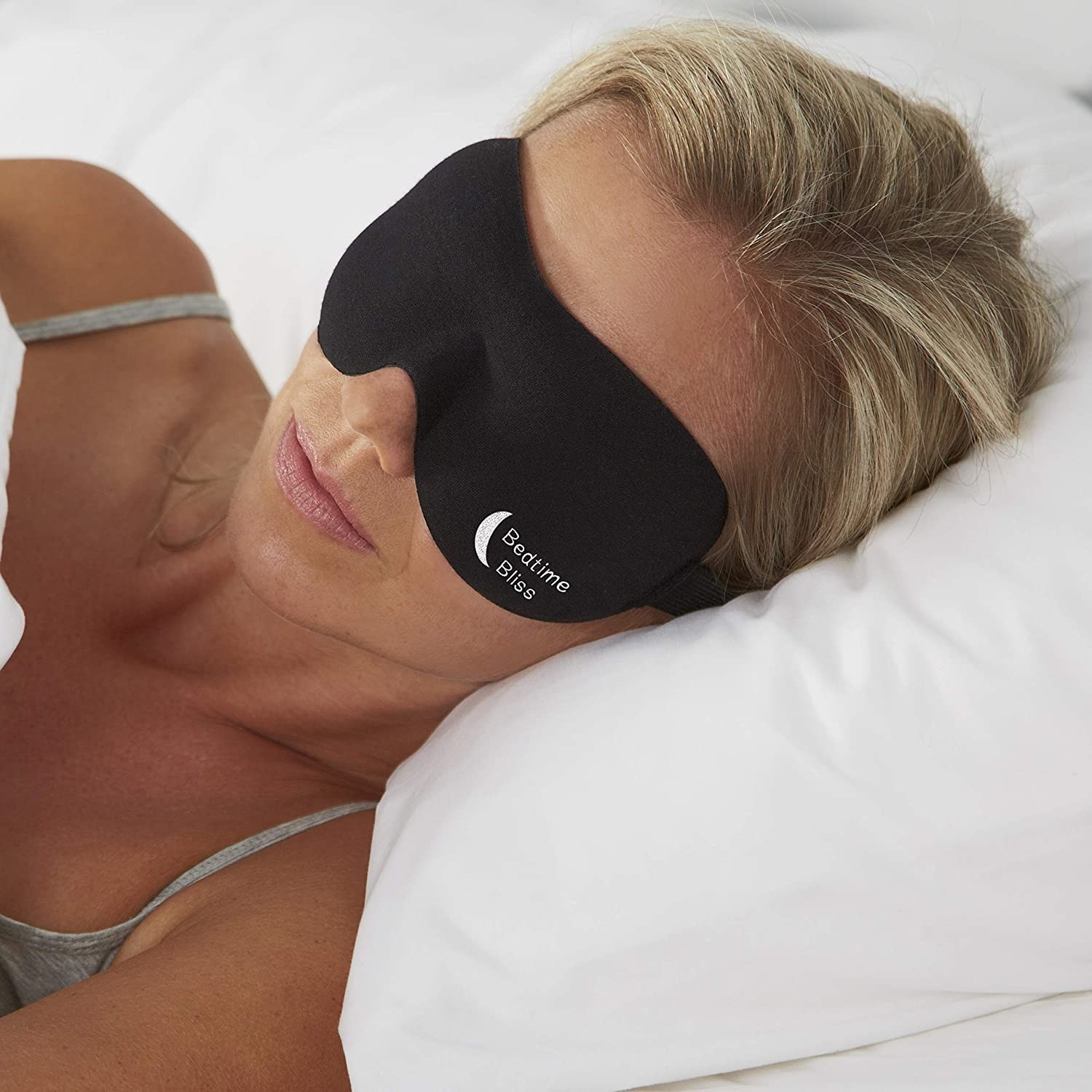 Person sleeping in bed with mask over their eyes